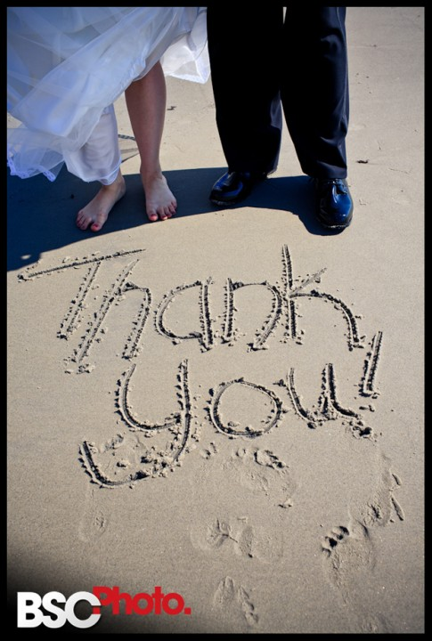 Connecticut wedding Photographers capture bride and groom writing in the sand